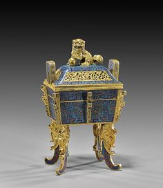 """Heavy and finely cast, Chinese gilt bronze and cloisonné enamel censer; of archaistic bronze form, set on four tall curvilinear legs, with upright handles; a lion finial to cover, and with taotie-like motifs on turquoise ground; four-character seal mark; H: 7 3/4"""""""