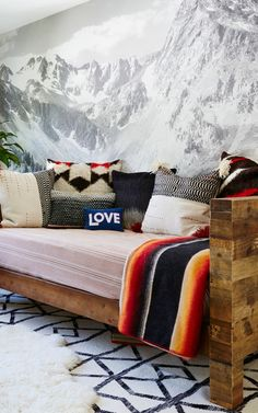 This custom black and white mountain range mural by MuralsWallpaper has been styled here by a customer as part of a cosy, boho living room look. Great inspiration for what you can do with the wall behind your couch! | Make your room a sight to behold with our stunning Mountain wallpaper murals. From Mount Everest to Mount Fuji, our mountain murals will create an awe-inspiring feature wall to get your wanderlust flowing and make your friends green with envy.