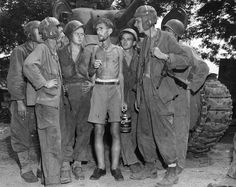 U.S. Soldiers listen to Mr. Bernard Herzog as he tells them of his days as an internee at Santo Tomas, Manila, Philippines, Feb. 1945 by John T Pilot, via Flickr. Mr. Herzog lost 78 pounds and is suffering from beriberi.