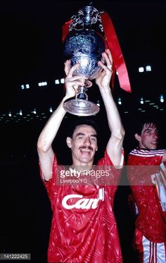 LIVERPOOl ENGLAND MAY 26 Liverpool's Ian Rush lifts the Football League Division one trophy aloft with Gary Ablett to his right holding the Barclays Trophy as Liverpool are crowned champions of...