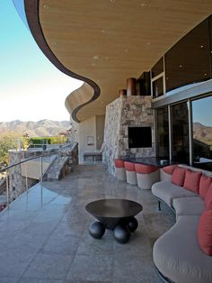 Landscape-Inspired Patio--This lavish Palm Springs patio featured on HGTV's Million Dollar Rooms draws inspiration from its surroundings. The curved roofline and sofa emulate the rise and fall of the mountain range, while the muted color scheme melds seamlessly with the view.