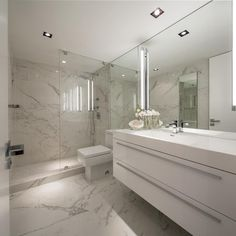 This luxurious bathroom is the perfect place to relax after a long day at the beach. The marble of the walls and the floor gives the space an elegant feel, while the clean lines and bright white color of the vanity makes the space feel fresh and bright.