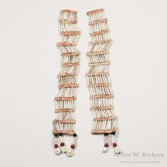 Sioux dentalium shell earrings strung on sinew and separated by a strip of red dyed raw hide. Each band has 10 dentilium shells.