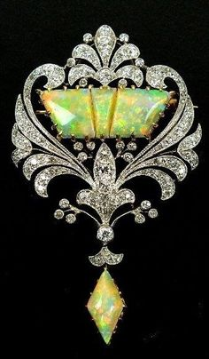 An early 20th century diamond and opal set brooch, designed as a three panel opal centre within old cut diamond set openwork scroll border, all supporting opal drop, all claw, collet and pave set in yellow and white metal, the reverse with detachable brooch. by chrystal