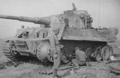 A Tiger with more problems than just a thrown track. Looks like this soldier is replacing a road wheel too...