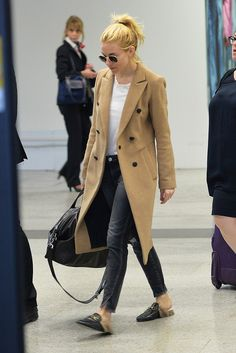 Sienna Miller wears a white t-shirt, camel coat, black jeans, Gucci loafers, and round sunglasses