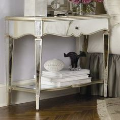 One-drawer mirrored nightstand.         Product: Nightstand   Construction Material: Wood and mirrored glass   Color: Silver   Features:   Part of the Jessica McClintock collection   Drawer and shelf for storage       Dimensions: 29 H x 32 W x 17 D