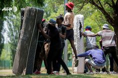 Students from Vaal University of Technology (VUT) take cover behind mattresses during clashes with South African anti-riot police and campus security at a demonstration in support of the Fees Must Fall Movement in Vanderbijlpark on October 13, 2016....