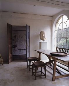 Axel Vervoordt. Monastic simplicity, with a bit of modern primitivism in the drawings on the wall. The French doors that peek into the next space are more compelling than the view from the arched window.