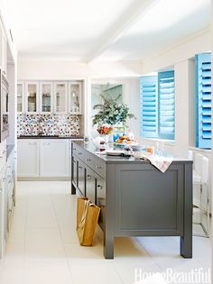 Shutters painted in Benjamin Moore Aura in Old Blue Jeans bring a bright English country note into this urban kitchen in New York City designed by Incorporated Architecture & Design.