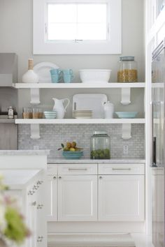 Another angle of Molly Frey designed kitchen -- other side of oven -- open shelves; lovely dishes, pale blue bowls, clear glass canisters; white pitchers against grey/white tile and greyish walls