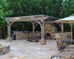 Free standing pergola with stone outdoor fireplace and iron furniture
