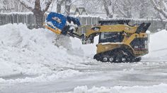 A plow clears snow from a commercial lot on Pilot House Drive on Thursday morning in Newport News. (Photo by Kaitlin McKeown / Daily Press)