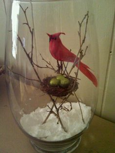 "a bird with a nest filled with tiny ornaments, all in a vase filled with ""snow"""