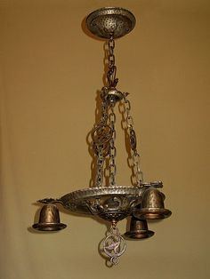 A Virden cast iron, dog;s head hanging fixture with original oval link chain.  http://www.vintagelights.com/product/1/vintage-cast-iron-3-bulb-dogs-head-hanging-fixture.html