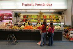Este es un exterior de la fruiteria. Se venden muchas frutas como manzanas, uvas y plátanos.