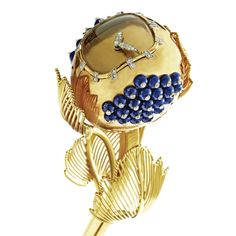 18 KARAT GOLD, DIAMOND AND LAPIS LAZULI FLOWER CLOCK, CARTIER, PARIS, CIRCA 1965 The stylized flower set at the sides with lapis lazuli beads, studded with round and single-cut diamonds, the plain dial showing pavé-set diamond hands, the stem supporting openwork gold leaves, the base set with panels of mosaic lapis lazuli