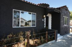 Black does not have to be reserved for modern structures. It works on any style house, such as this Spanish one. It actually makes small bungalows look bigger and more formidable