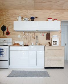 Plywood Cottage Kitchen  Glossy white cabinets add a modern touch in a deconstructed space.