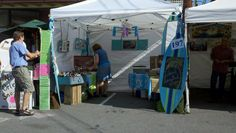 Affordable booth ideas for arts and craft festival - surfboard cut out sign and suit case display boxes.