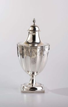 """Paul Revere, Patriot (1734-1818): Rare and Important Boston Federal Silver Sugar Urn and Cover, Circa 1800 - Of cylindrical form, engraved with a border of medallions suspending tasseled drapery swags beneath a vine border at the rim, an oval medallion enclosing the initials """"WMH"""" in foliate script & date """"1800,"""" the circular foot with matching vine border above the square base engraved with a tripartite leaf at each corner... marked """"REVERE"""" within rectangle on one side of the base. H 9 1/4 in"""