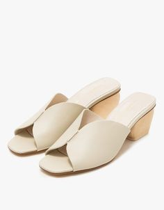 From Intentionally Blank, a sculptural mule in Bone. Open toe. Leather lining. Padded footbed. Wooden block heel with rubber cap. • Leather upper • Leather sole • Women's sizes listed