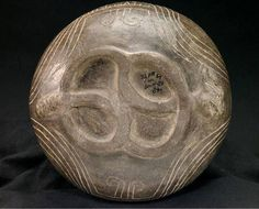 Mississippian culture vessel from the Berry site in Missouri. Features an incised feline motif. This photo shows the bottom of the cat vessel. What's neat about this pot is that it combines two creatures typically associated with the Mississippian Lowerworld - i.e., the cat and serpent. In this photo you can actually see the rattles on the serpent's tail on the left side and the critter's head on the right side.