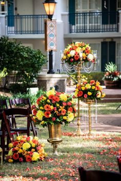 Disney Fairy Tale Wedding ceremony floral of red, orange, and yellow flowers down the aisle at Disney's Port Orleans - Riverside Oak Manor Lawn