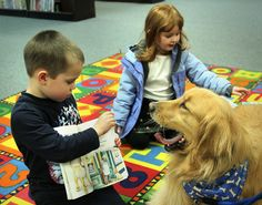 Chase Norkus, 5, of Braintree, reads to Merryl, a golden retriever, who lets out a yawn while visiting the Children's Room of the Tufts Library,Thursday, March 2, 2017. Suniya Goodwin, 4, of Weymouth, listens, as well. Gary Higgins/The Patriot Ledger