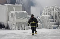 Fire fighter walks around an ice-covered warehouse that caught fire in Chicago on January 23, 2013.