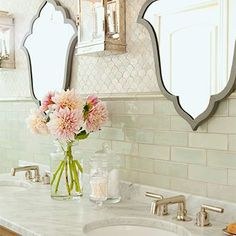 Bathroom with varying backsplashes and unique mirror shapes.