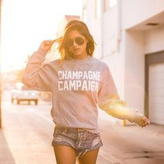 """The Private Party Champagne Campaign Sweatshirt in Grey is constructed from pill-resistant fleece and features a crew neck with a relaxed fit. """"CHAMPAGNE CAMPAIGN"""" is screen printed on the front."""