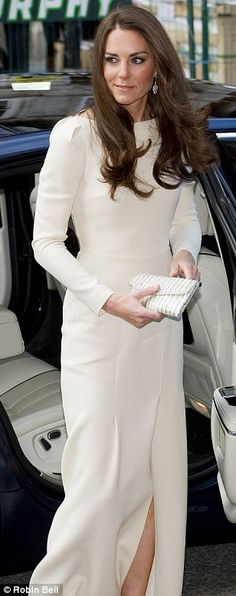 The Duchess is wearing what is believed to be a 2009 creation by designer Roland Mouret.  Simple & elegent, cream, floor-skimming gown with slit to the thigh.   Boat-neckline and long sleeves.  Paired with crystal Jimmy Choo shoes, and a diamante clutch bag.