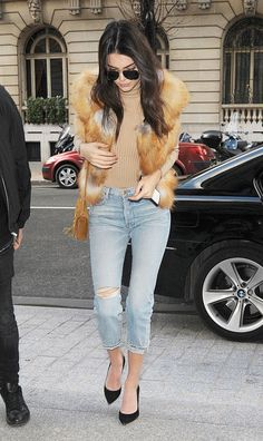 While out and about in Paris, the model elevated her distressed denim with a camel colored turtleneck, matching fur vest, and pointy toe black pumps.