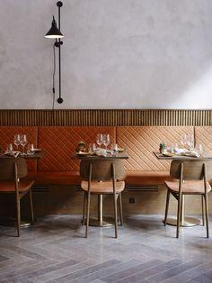 Gennemtænkt indretning med grå vægge og gulv, cognacfarver på quilted læder og sæde og træpaneler og træstole