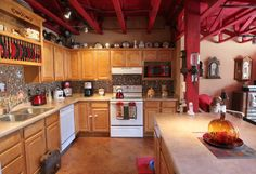 Fun kitchen with red beamed ceiling.