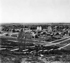 A portion of Delta, Colorado; shows houses, a wood sidewalk, stairs, churches, and commercial buildings. Bluffs and plains of the Gunnison River Valley are in the background.   Date  [1910?]    :: History Colorado