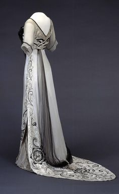 """Evening dress belonging to Queen Maud of Norway, 1910-13. Machine-woven silk fabrics in satin and plain weave, tulle. Hand-embroidered with silk threads and glass beads, passementerie. Photo: Teigens Fotoatelier / The National Museum of Art, Architecture and Design, Oslo. According to the book """"Style & Splendour: The Wardrobe of Queen Maud of Norway, 1896-1938,"""" Queen Maud may have worn the dress while in mourning for her father Edward VII, who died on 6 May 1910."""