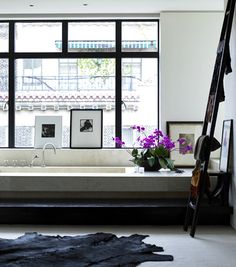 perfect modern bath, complete with big windows, orchids, and a cowhide rug.