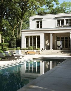 Grey slate tiles make the pool water look deep blue. The neoclassical façade of fashion designers Joe Mimran and Kimberley Newport-Mimran's house — designed by architect Gordon Ridgely with landscaping by Ron Holbrook — is elegantly clad in Indiana limestone. The terrace uses the same material for a seamless look.