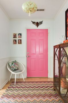 The front entrance starts with a burst of color! Door paint is Valspar Frosty Berry. The wall and molding paint is Valspar Swiss Coffee and Valspar Quail Egg. The rug is Dash and Albert ZigZag Hooked Rug.
