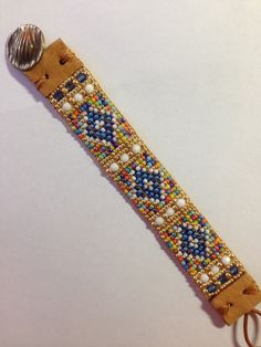 Southwestern style, Sundance style, rainbow of colors seed beads. Blues, whites,lime,orange,yellow and gold. Hand loomed Leather end tabs Brass grasses button  Quality and durable Use zoom under photos to see detail. Galvanized gold seed beads, blue and white Czech glass faceted beads, seed beads  Measures 7 3/8 inches in total length. Beaded portion measures 4 3/4 in length. 7/8 inches wide. This is not adjustable. Will fit wrist size up to approximately 6 1/2 inches. Shi...