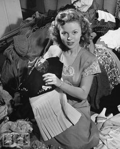 Shirley Temple Donates Clothes for War Relief. The 17-year-old actress, who had starred in several home front morale-boosting movies during World War II, gathers her old outfits at home in Hollywood in April, 1945 for a clothing drive.