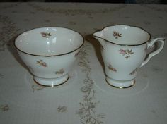 """Large cream and sugar in a pink Rosebud with gold leaves pattern, gold accenting  The creamer is 3 3/4"""" (9.5 cm) high x 3 3/8"""" (8.6 cm) at the brim and the sugar bowl is 3 3/16"""" (8.1 cm) high 4 11/16"""" (11.9 cm) at the brim  Made of bone china from England by Royal Stafford  This set is in very good condition and only appears to have seen use as a collectible    These items have no nicks, chips, cracks, or signs of repair 