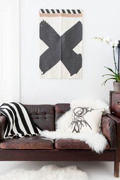 black & white art print, brown leather sofa, sheepskin throws, striped blanket & a white orchid #homedecor #interiordesign