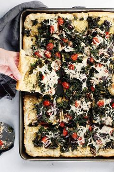 Vegan Crispy Kale Grandma-Style Pizza by Pasta-based. Made in a cookie sheet, this rectangular pizza is topped with crispy kale, homemade cashew ricotta, vegan mozzarella, grape tomatoes, mushrooms, and kalamata olives.
