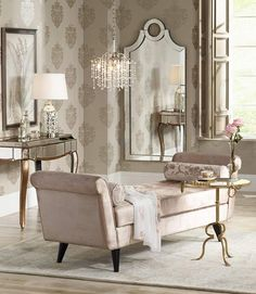 Elegant bedroom including a mirrored vanity table, beige velvet chaise, and gold and glass side table
