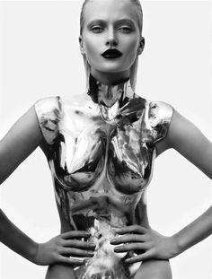 Bold Metallics. Strong makeup. Chiseled dimensions of the face contrast with the fluid body suit.