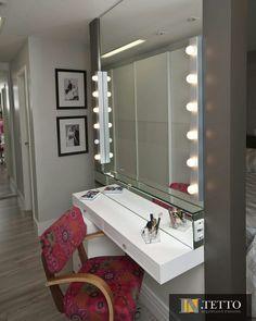 Um quarto de casal moderno e aconchegante. Em tons neutros e cabeceira com iluminação a LED. Ponto de destaque da composição é o painel posicionado ao centro do quarto, que em uma face é utilizado como painel para TV e na outra face é um espaço perfeito para a beleza feminina, que conta amplo espelho com iluminação especial. Esse incrível projeto ergonômico, que une aproveitamento de espaço, beleza e praticidade é assinado por Rosangela Pimenta, Rafael Gomez e Tereza Bissoto.