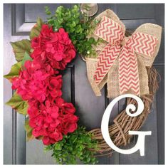 This bright, vibrant wreath with red hydrangeas and green eucalyptus tied together with a red chevron and burlap bow is perfect to hang on your door for the holidays! Pictured with a cream monogram, choose the color and the initial monogram you would like to make it personal.